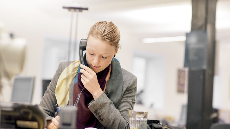 Woman sitting in an office and talking on the phone